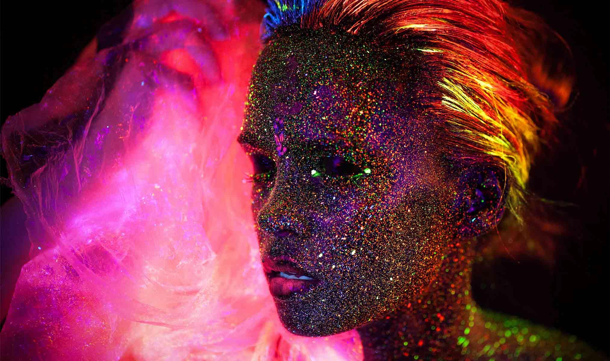 Artystyczny makijaż wykonany farbami ultrafioletowymi przedstawiający muzę z efektami specjalnymi