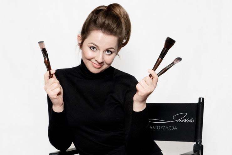 Makijażystka Kasia Zielińska pokazuje pędzelki do makijażu siedząc na krześle charakteryzatorskim