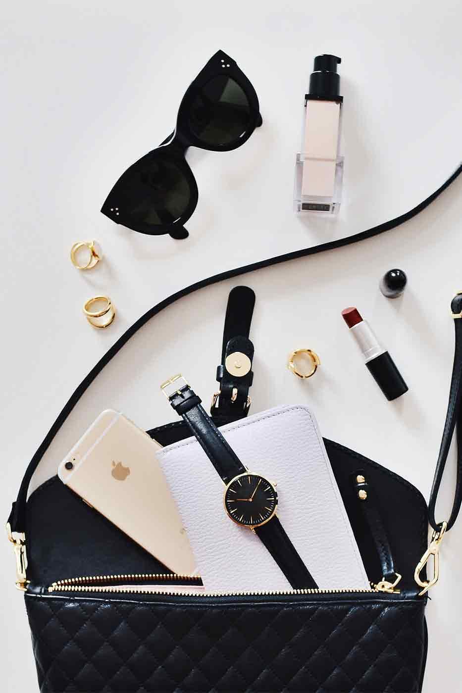 damska torebka w kolorze czarnym z rozsypanymi kosmetykami jak podkład i szminka