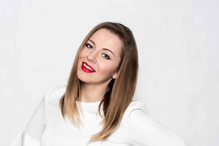 Katarzyna Zielińska w rozświetlającym makijażu białej koszuli na białym tle