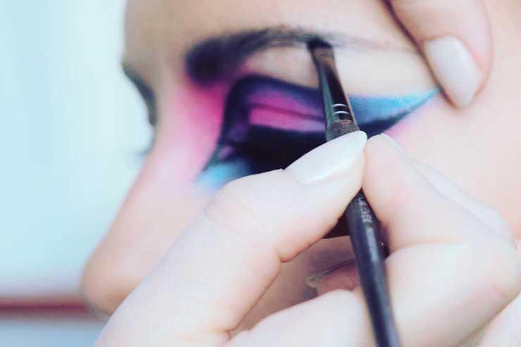 Mocny makijaż typu cut crease niebiesko fioletowy z ciemna brwią